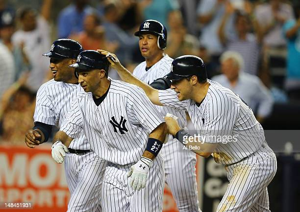 Raul Ibanez of the New York Yankees is met by Mark Teixeira Robinson Cano and Alex Rodriguez after hitting a grand slam against the Toronto Blue Jays...