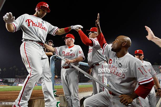 Raul Ibanez of the Philadelphia Phillies get congratulated by his teammates including Jimmy Rollins as he enters the dugout after hitting a three run...