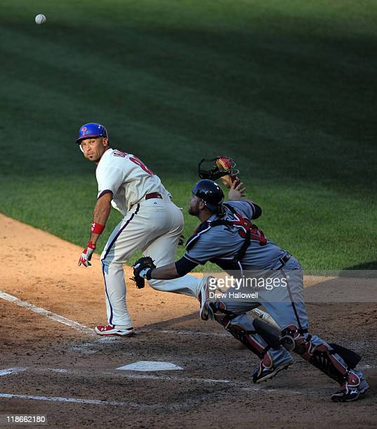 Raul Ibanez of the Philadelphia Phillies runs towards first base as Brian McCann of the Atlanta Braves goes for the ball at Citizens Bank Park on...