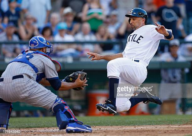 Raul Ibanez of the Seattle Mariners slides into home against catcher Welington Castillo of the Chicago Cubs while trying to score on a single by...