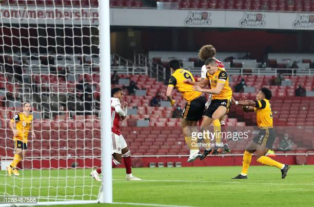 Raul Jimenez and Conor Coady of Wolverhampton Wanderers collide with David Luiz of Arsenal during the Premier League match between Arsenal and...