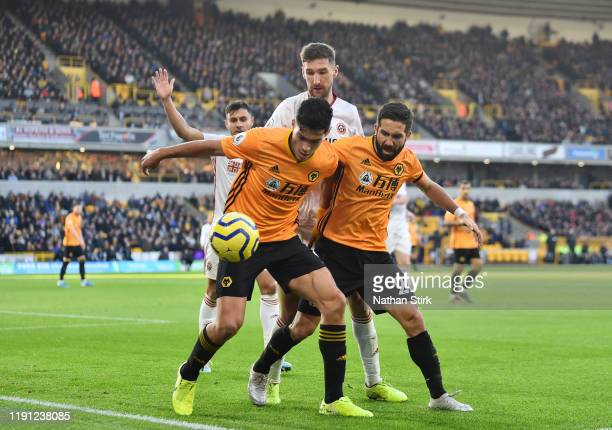Raul Jimenez and Joao Moutinho of Wolverhampton Wanderers shield the ball during the Premier League match between Wolverhampton Wanderers and...
