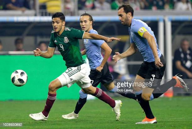 Raul Jimenez of Mexico brings the ball up the field as Diego Godin of Uruguay pursues in the first half during the International Friendly match...
