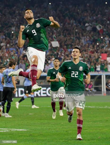 Raul Jimenez of Mexico celebrates with Hirving Lozano after scoring on a penalty kick against Uruguay in the firtst half during the International...