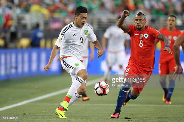 Raul Jimenez of Mexico drives the ball as Arturo Vidal of Chile defends during a Quarterfinal match between Mexico and Chile at Levi's Stadium as...
