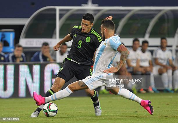 Raul Jimenez of Mexico drives the ball as Nicolas Otamendi of Argentina defends during a friendly match between Argentina and Mexico at ATT Stadium...