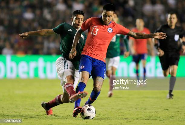 Raul Jimenez of Mexico fights for the ball with Erick Pulgar of Chile during the international friendly match between Mexico and Chile at La...