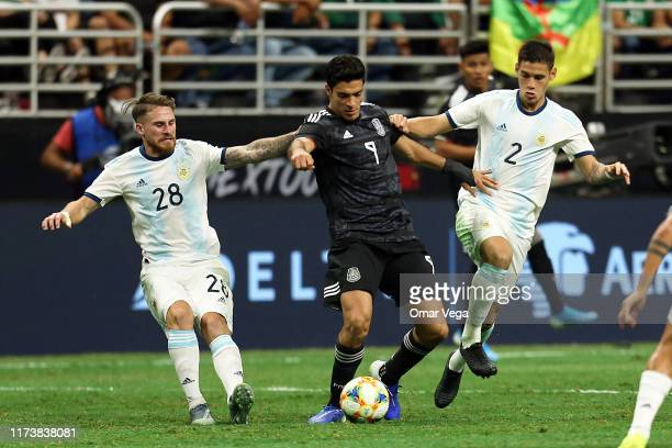 Raul Jimenez of Mexico fights the ball with Alexis Mac Allister and Lucas Martinez Quarta of Argentina during the international friendly match...