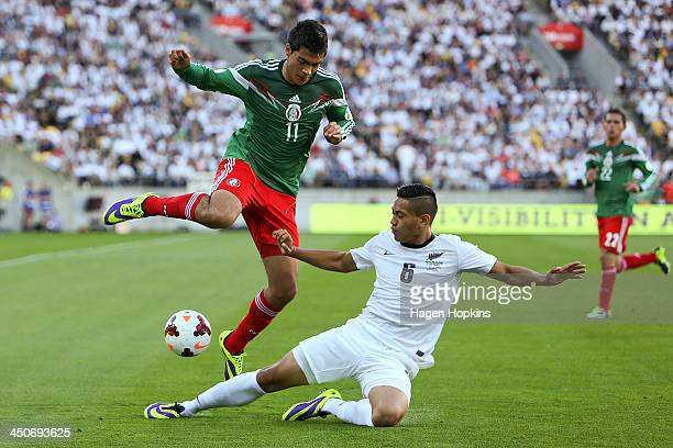 Raul Jimenez of Mexico is tackled by Bill Tuiloma of New Zealand during leg 2 of the FIFA World Cup Qualifier match between the New Zealand All...