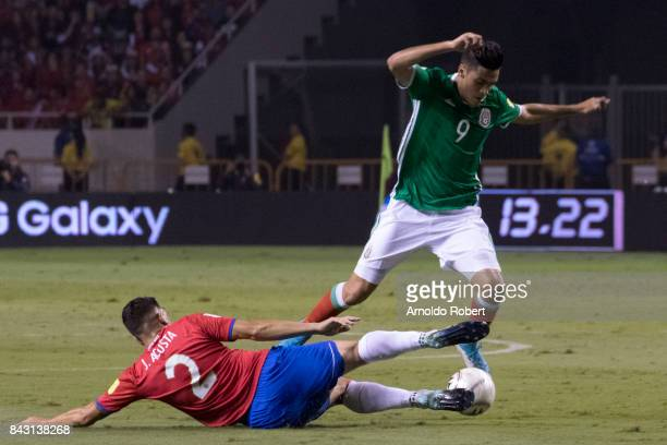 Raul Jimenez of Mexico tries to avoid the slide by Johnny Acosta of Costa Rica during the match between Costa Rica and Mexico as part of the FIFA...