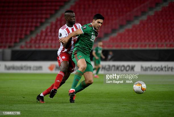 Raul Jimenez of Wolverhampton Wanderers and Ousseynou Ba of Olympiacos FC during the UEFA Europa League round of 16 first leg match between...
