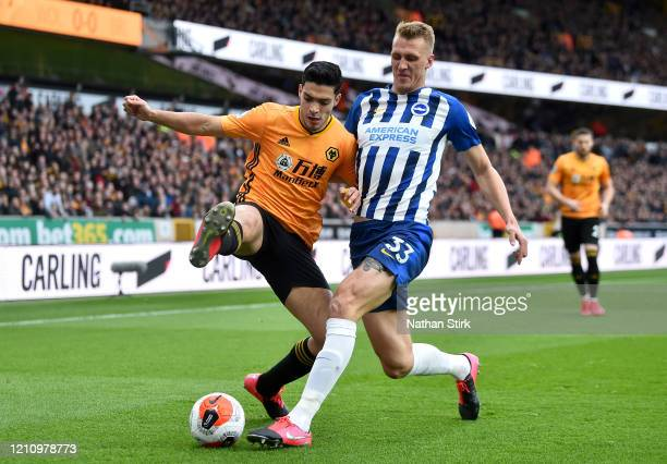 Raul Jimenez of Wolverhampton Wanderers battles for possession with Dan Burn of Brighton and Hove Albion during the Premier League match between...