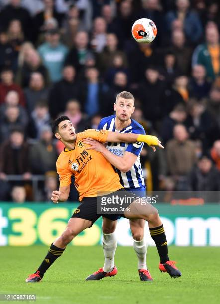 Raul Jimenez of Wolverhampton Wanderers battles for possession with Adam Webster of Brighton and Hove Albion during the Premier League match between...