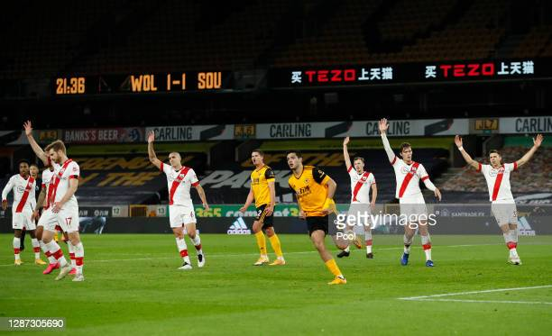 Raul Jimenez of Wolverhampton Wanderers celebrates scoring a goal that is later ruled for offside as Stuart Armstrong, Oriol Romeu, James...