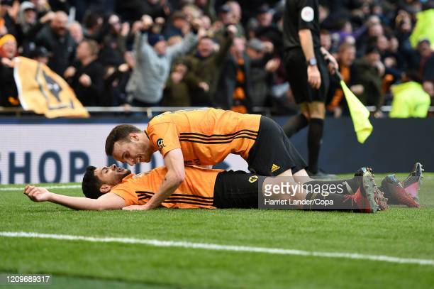 Raul Jimenez of Wolverhampton Wanderers celebrates with teammate Diogo Jota after scoring his team's third goal during the Premier League match...