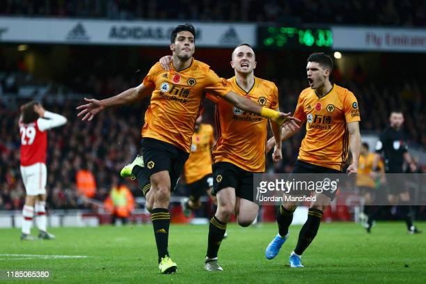 Raul Jimenez of Wolverhampton Wanderers celebrates with teammates Diogo Jota and Ruben Vinagre after scoring his team's first goal during the Premier...