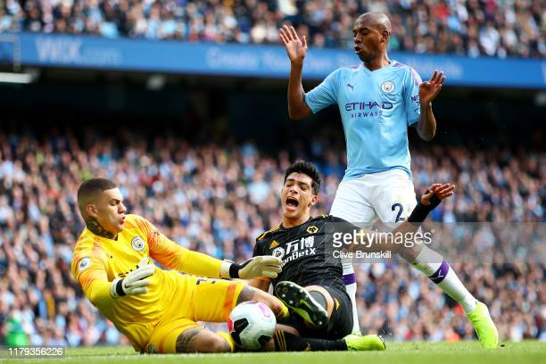 Raul Jimenez of Wolverhampton Wanderers challenges Ederson of Manchester City for the ball during the Premier League match between Manchester City...