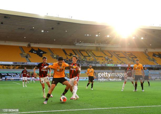 Raul Jimenez of Wolverhampton Wanderers is challenged by Harry Wilson of AFC Bournemouth during the Premier League match between Wolverhampton...