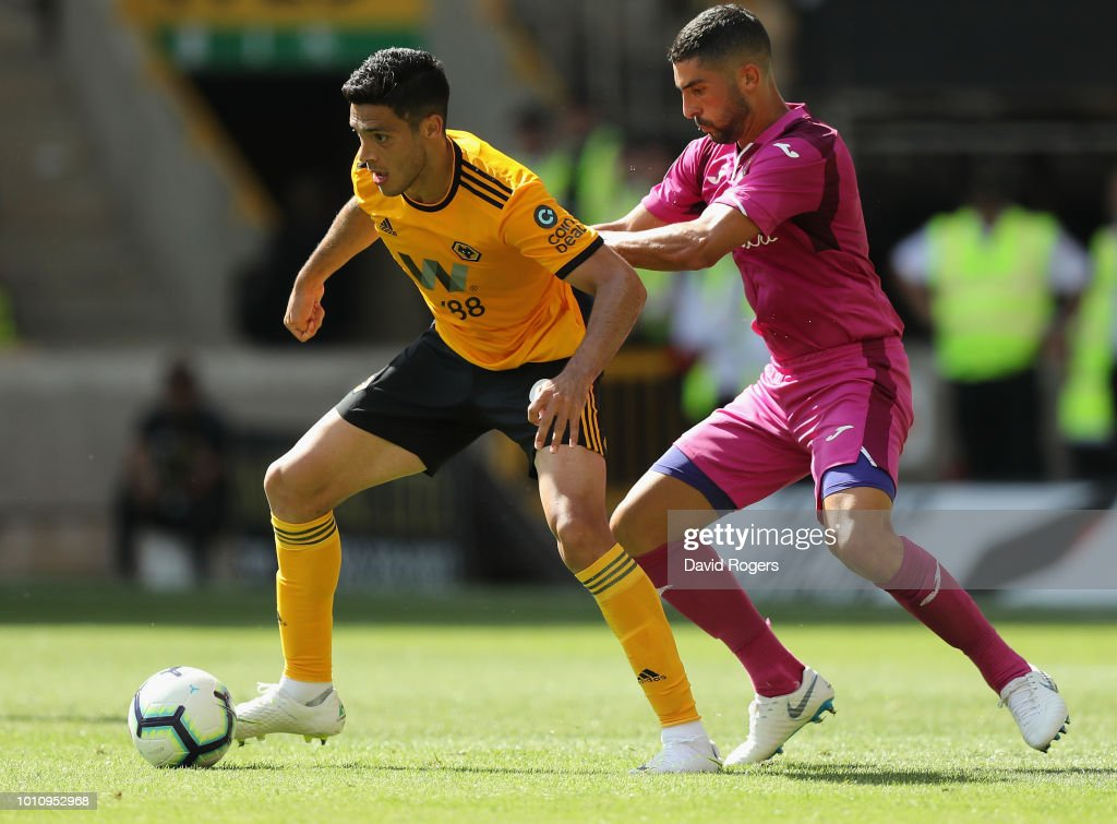 Raul Jimenez of Wolverhampton Wanderers is watched by Alvaro Gonzalez during the pre-season friendly match between Wolverhampton Wanderers and Villareal at Molineux on August 4, 2018 in Wolverhampton, England.