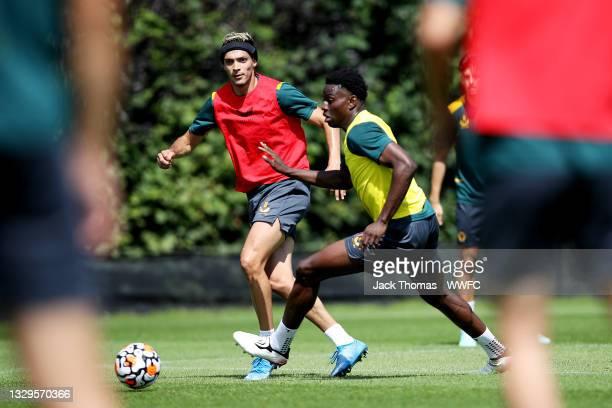 Raul Jimenez of Wolverhampton Wanderers passes the ball under pressure from Owen Otasowie of Wolverhampton Wanderers during a Wolverhampton Wanderers...