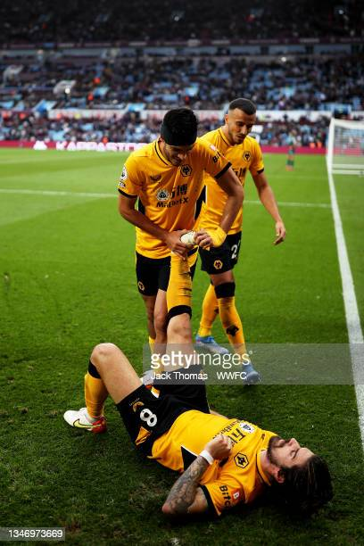 Raul Jimenez of Wolverhampton Wanderers stretches out Ruben Neves leg after Ruben Neves scored his team's third and match winning goal during the...