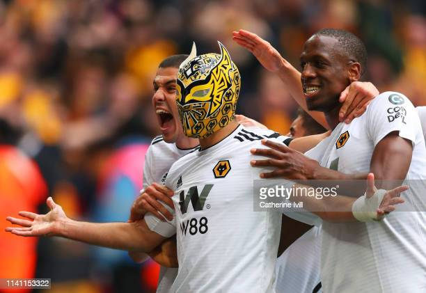 Raul Jimenez of Wolverhampton Wanderers wears a mask as he celebrates scoring his team's second goal with team mayes Conor Coady Willy Boly and...