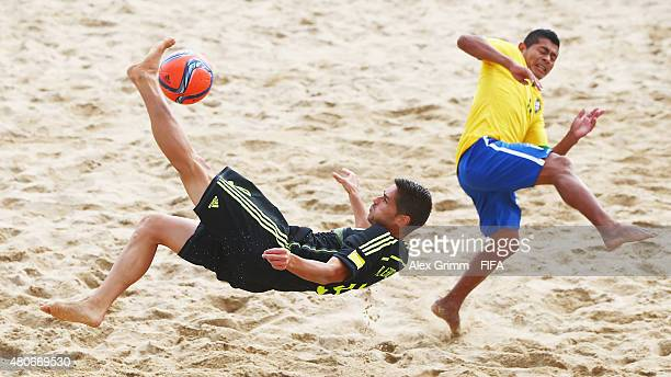 Raul Merida of Spain does a bicycle kick next to Datinha of Brazil during the FIFA Beach Soccer World Cup Portugal 2015 Group C match between Brazil...