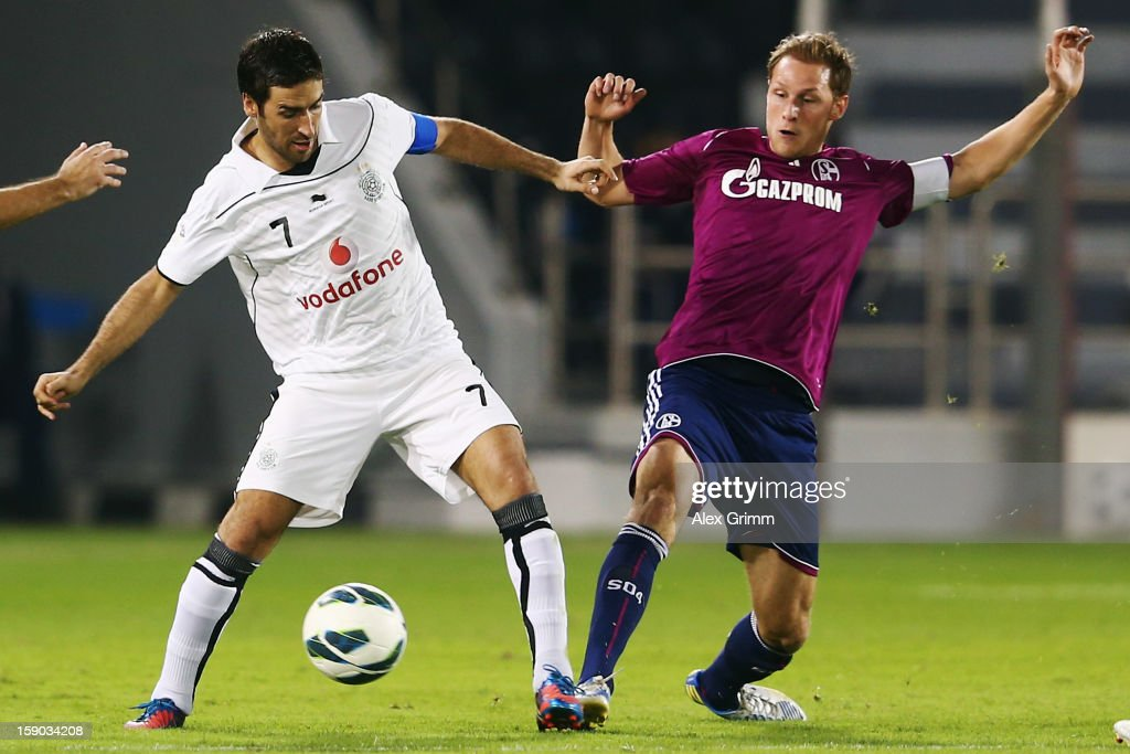 Raul (L) of Al Sadd is challenged by Benedikt Hoewedes of Schalke during the friendly match between Al-Sadd Sports Club and FC Schalke 04 at Jassim Bin Hamad Stadium on January 6, 2013 in Doha, Qatar.