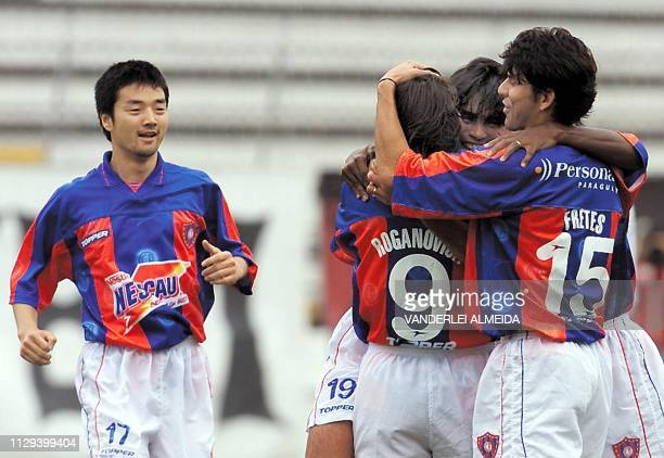 Raul Roganovich of the Paraguyuan team is hugged by teammate Fretes as Nozomi Hiroyama looks on after converting the first goal against Brazilian...