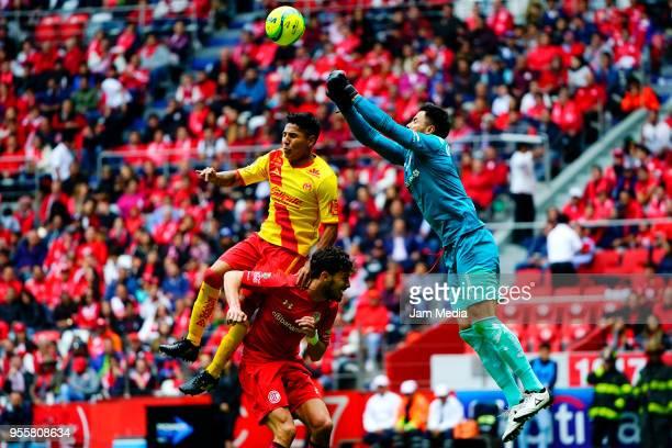 Raul Ruidiaz of Morelia Santiago Garcia of Toluca and Alfredo Talavera of Toluca fight for the ball during the quarter finals second leg match...