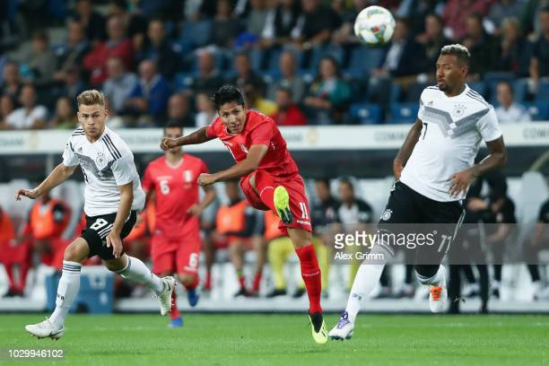 Raul Ruidiaz of Peru takes a shot on the goal under pressure from Joshua Kimmich and Jerome Boateng of Germany during the International Friendly...