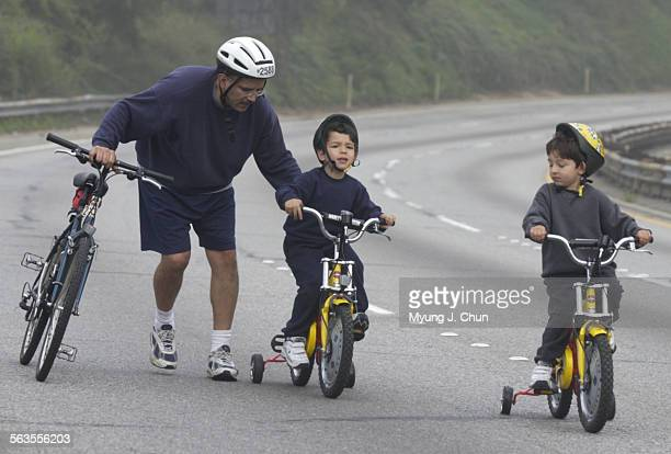 Raul Salinas of Pasadena helps out his son Nicholas Salinas on the uphill portion of the 110 Pasadena Freeway during Sunday morning's Arroyo Fest....