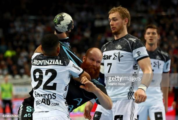 Raul Santos and Rene Toft Hansen of Kiel challenge Alexander Becker of Gummersbach for the ball during the DKB HBL Bundesliga match between THW Kiel...