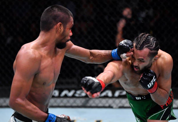 Raulian Paiva of Brazil punches Kyler Phillips in their bantamweight fight during the UFC Fight Night event at UFC APEX on July 24, 2021 in Las...