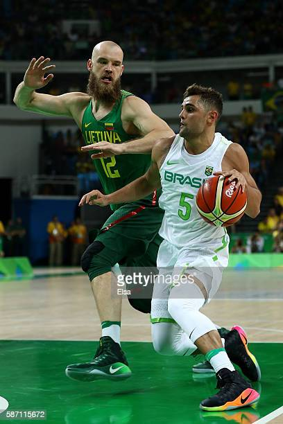 Raulzinho Neto of Brazil drives the ball against Antanas Kavaliauskas of Lithuania during a Men's preliminary round basketball game between Brazil...