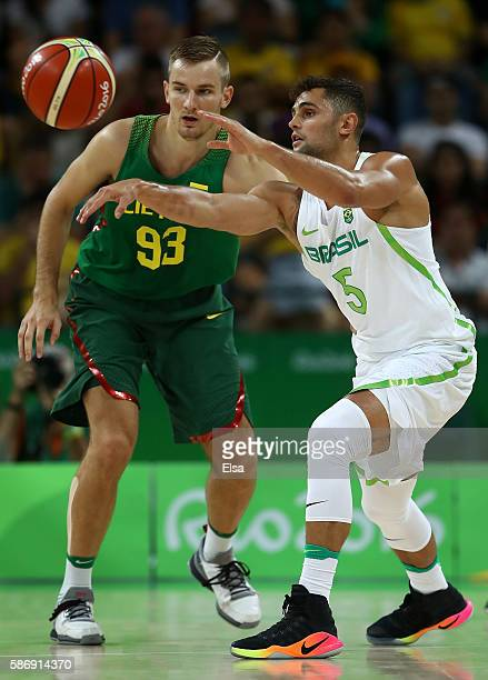 Raulzinho Neto of Brazil passes the ball against Vaidas Kariniauskas of Lithuania during a Men's preliminary round basketball game between Brazil and...