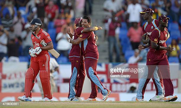 Ravi Bopara of England leaves the field as Dwayne Bravo and Ravi Rampaul of the West Indies celebrates winning the 1st One Day International between...