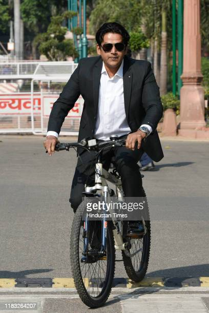 Ravi Kishan rides a bicycle during the first day of the winter session of Parliament on November 18 2019 in New Delhi India The 250th Rajya Sabha...