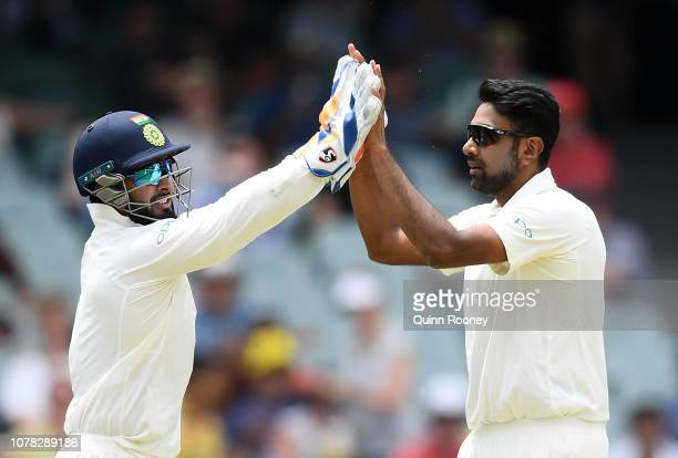 Ravichandran Ashwin and Rishabh Pant of India celebrate getting the wicket of Marcus Harris of Australia during day two of the First Test match in...