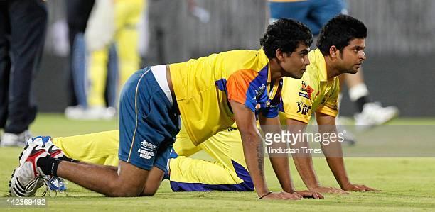 Ravindra Jadeja and Suresh Raina of the Chennai Super Kings stretch during net practice at MA Chidambaram Stadium on April 2 2012 in Chennai India...