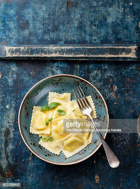 Ravioli pasta with mozzarella cheese and basil on blue backgroun