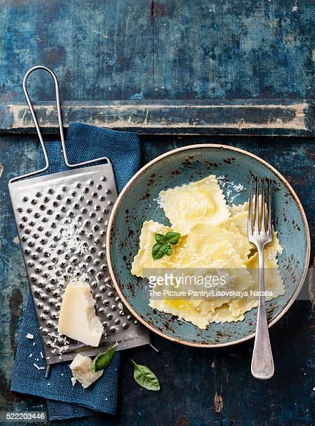Ravioli pasta with mozzarella cheese, basil and parmesan on blue