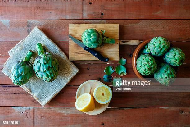 Raw artichokes and sliced lemon on wood