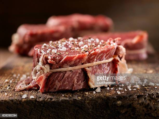 raw bacon wrapped steak fillets seasoned with salt and pepper - raw food stock pictures, royalty-free photos & images