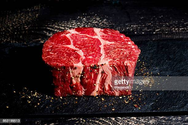 Raw beef and pepper on dark wood