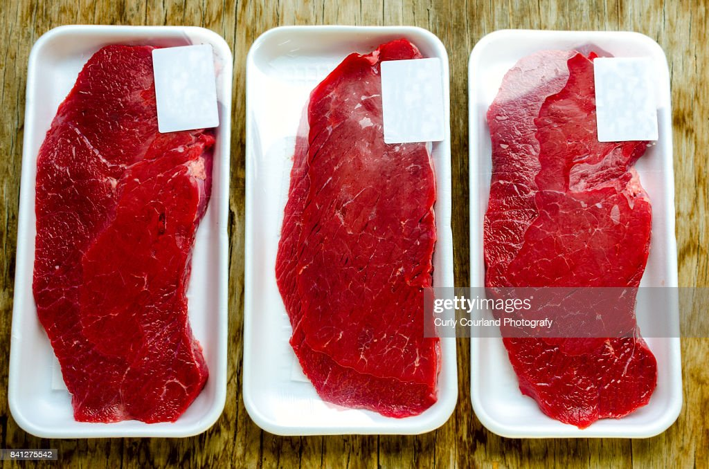 Raw beef schnitzels in the box wrapped with film : Stock Photo