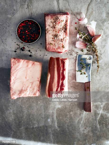 Raw beef short ribs with meat cleaver and peppercorns, overhead view