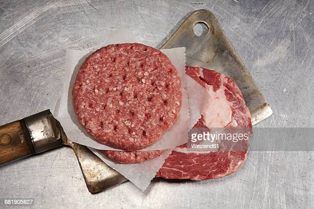 Raw beef steak and burger patty on cleaver