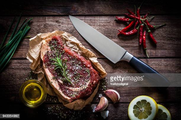 Raw beef steak on rustic wooden table