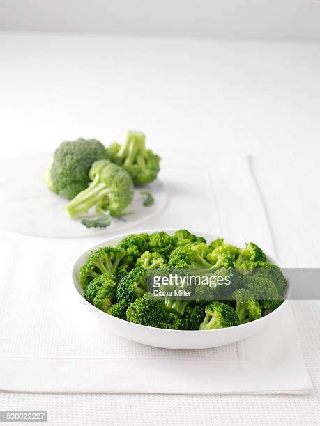 Raw broccoli on marble cutting board and bowl of boiled broccoli